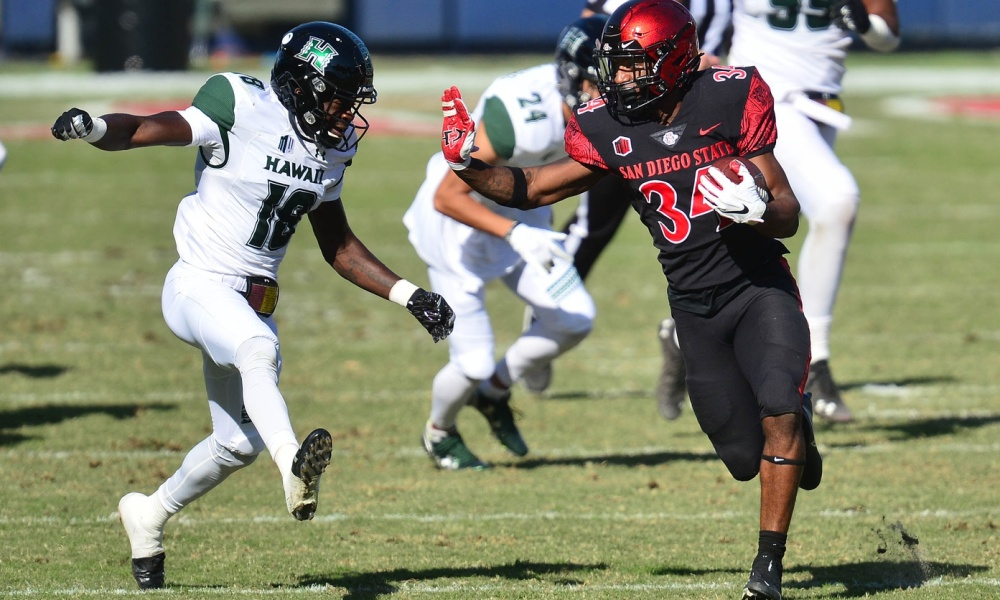 Nov 14, 2020; Carson, California, USA; San Diego State Aztecs running back Greg Bell (34) runs the ball against Hawaii Warriors defensive back Cortez Davis (18) during the first half at Dignity Health Sports Park. Mandatory Credit: Gary A. Vasquez-USA TODAY Sports